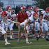 Hartman (red polo) warms up with the varsity football players before a game.