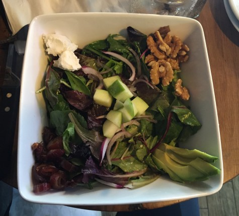 The Harvest contains mixed greens, apples, walnuts, dates, goat cheese, avocado, red onion, and cider vinaigrette