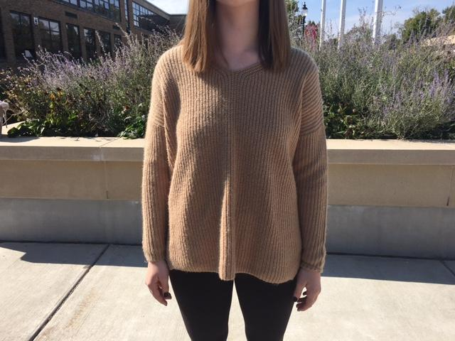 Emily Tomkinson is wearing a caramel colored sweater, perfect for fall