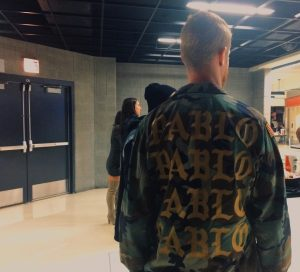 """One of West's fans models a camouflage army jacket with """"Pablo"""" written across the back in gold font at the United Center."""